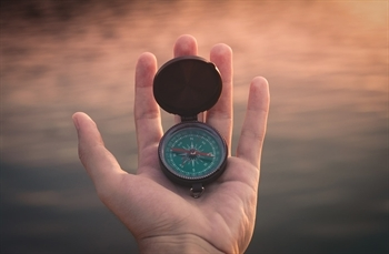 Hand holding compass. Photo Credit: Aron | unsplash.com