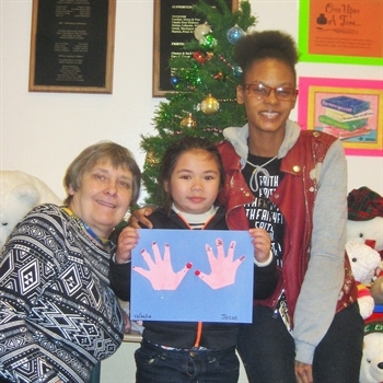 CWR Assistant Director, Maire Larkin (left) and Childcare Specialist, Tonnika Williams were happy to create crafty reindeer with a child excitedly displaying her work.