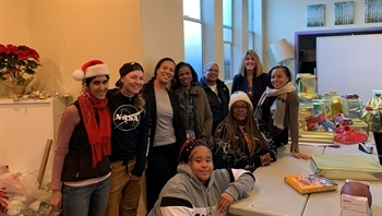 Cameo staff, participants, and San Francisco Adult Probation Department Chief gather with holiday gifts.