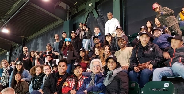 CJCJ's team gathers together with family and friends at a Giants Game for a staff appreciation event.