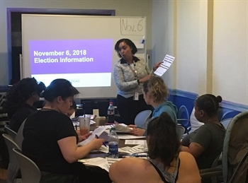 A representative from the SF Department of Elections discusses the upcoming election with Cameo House participants.